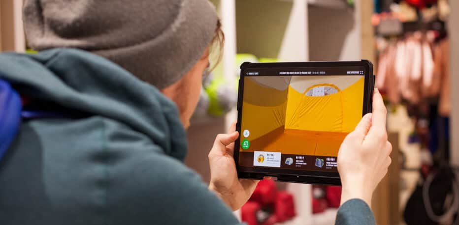 Man uses an iPad to test MEC's augmented reality app to view the retailers tents in their real size.